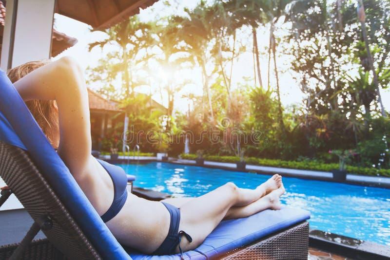 Frau, die im tropischen LuxusUrlaubshotel nahe Swimmingpool sich entspannt stockfotos