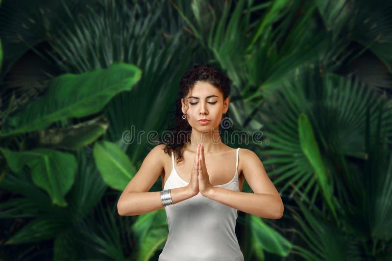Frau, die im tropischen Regenwald meditiert stockbilder