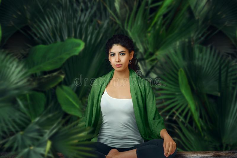 Frau, die im tropischen Regenwald meditiert lizenzfreie stockfotos