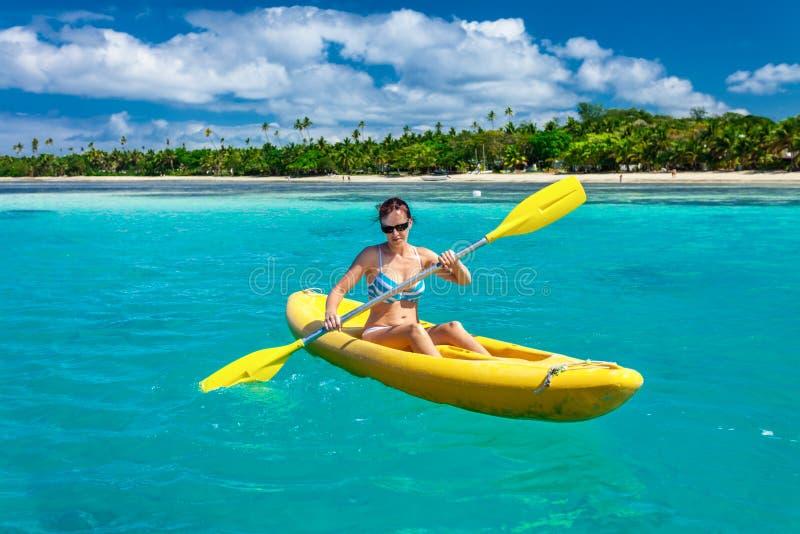 Frau, die im Urlaub im Ozean in tropischer Fidschi-Insel Kayak fährt stockfotos