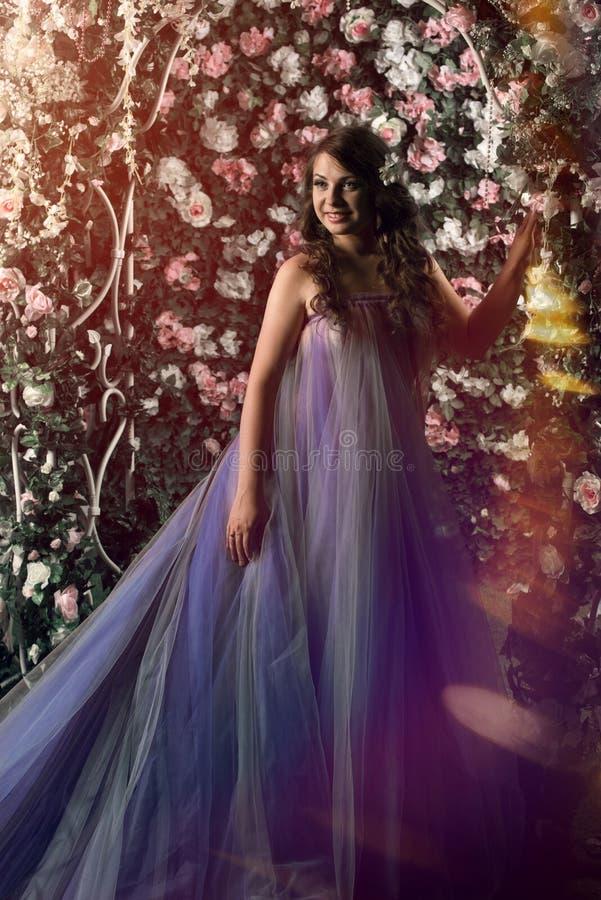 Frau, die im violetten langen Kleid unter Bogen von rosa und weißen Rosen steht lizenzfreies stockbild