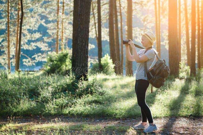 Frau, die im Wald auf Landschaft fotografiert stockbild
