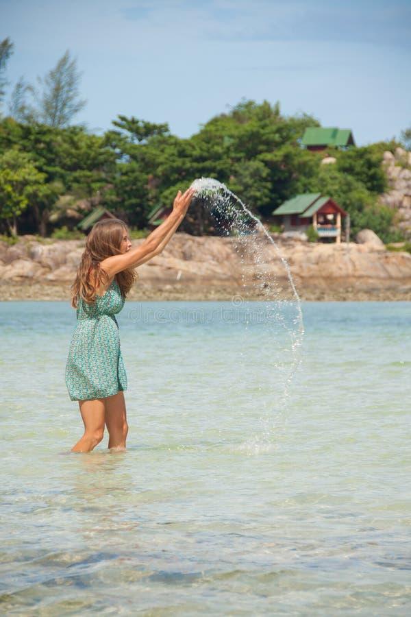 Frau, die im Wasser Knie-tief steht stockbild
