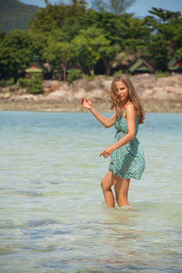 Frau, die im Wasser Knie-tief steht stockfotografie