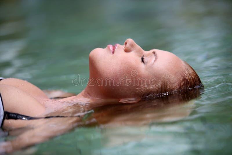 Frau, die im Wasser sich entspannt lizenzfreie stockfotos