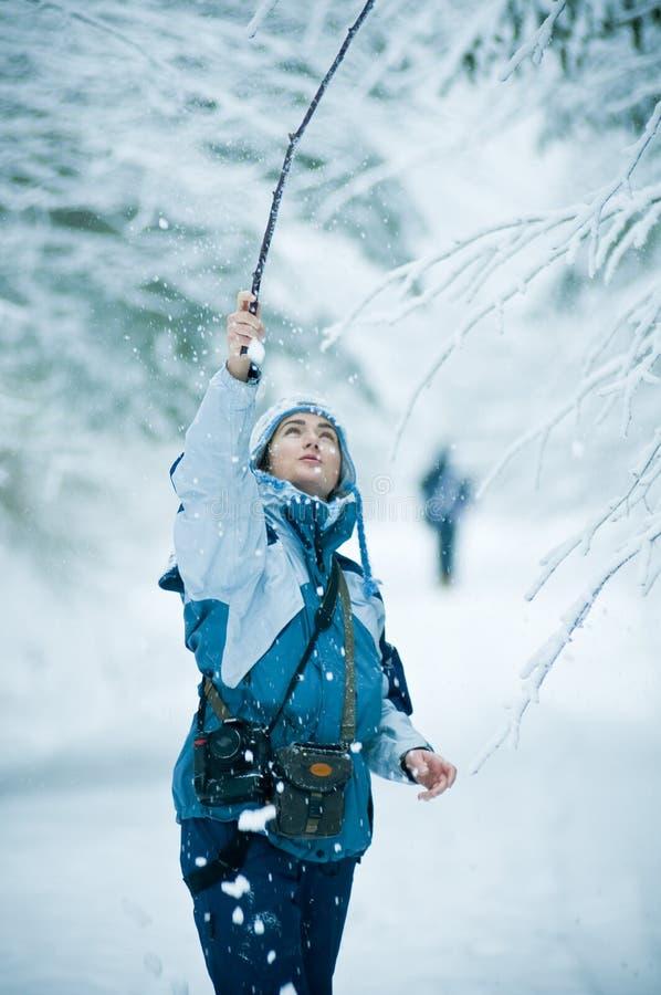 Frau, die im Winterschnee spielt stockfotos