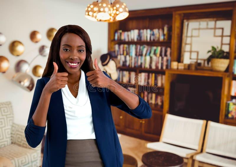 Frau, die im Wohnzimmer mit den Daumen oben lächelt stockfotos