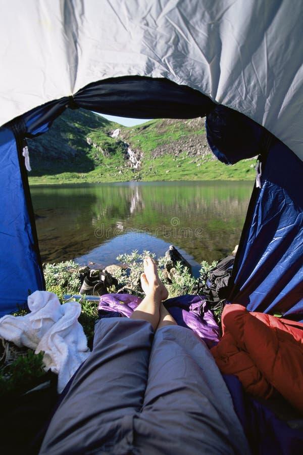 Frau, die im Zelt mit einer Ansicht von See liegt stockfotos