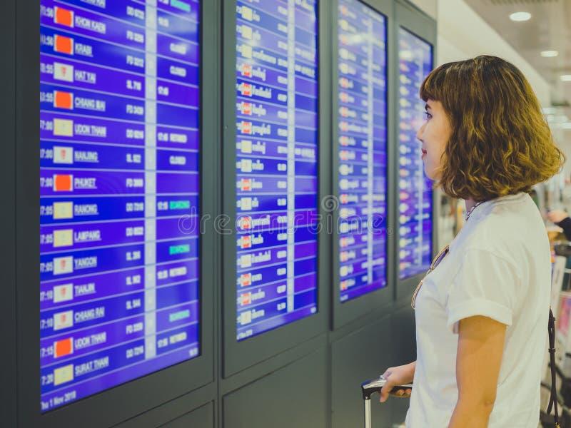 Frau, die Informationsbrett im Ausdruck des internationalen Flughafens betrachtet stockfotos