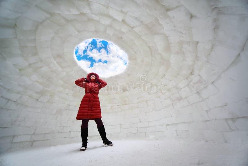 Frau, die inneren Iglu am Winter steht stockfotografie