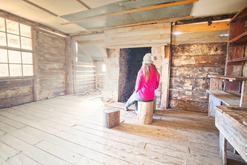 Frau, die innerhalb einer alten Bauholzhütte auf Klotzschemel Snowy-Bergen sitzt lizenzfreies stockfoto