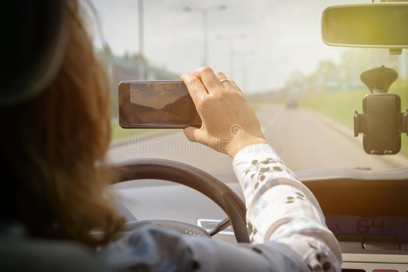 Frau, die intelligente Telefonkamera beim Fahren des Autos verwendet lizenzfreies stockfoto