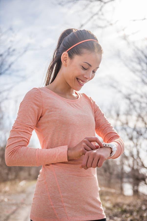 Frau, die intelligente Uhr der Eignung für das Laufen vorbereitet Sportlerin, die zum Morgenlauf in der kalten Natur der Frischlu stockfotos