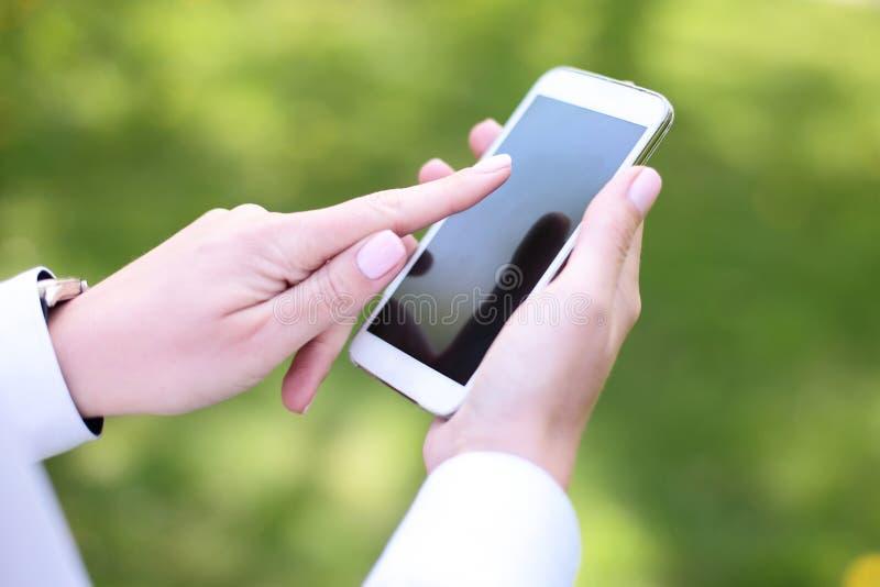 Frau, die intelligentes Mobiltelefon im Park verwendet lizenzfreie stockfotos