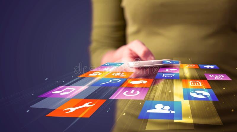 Frau, die intelligentes Telefon mit bunten Anwendungsikonen hält stockfoto