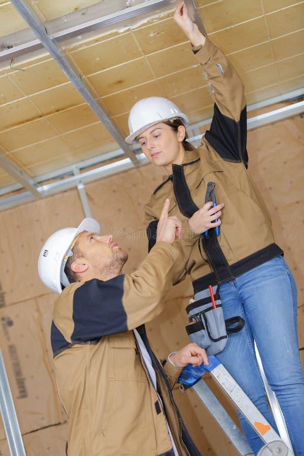 Frau, die Isolierung im Dachboden niederlegt stockfoto