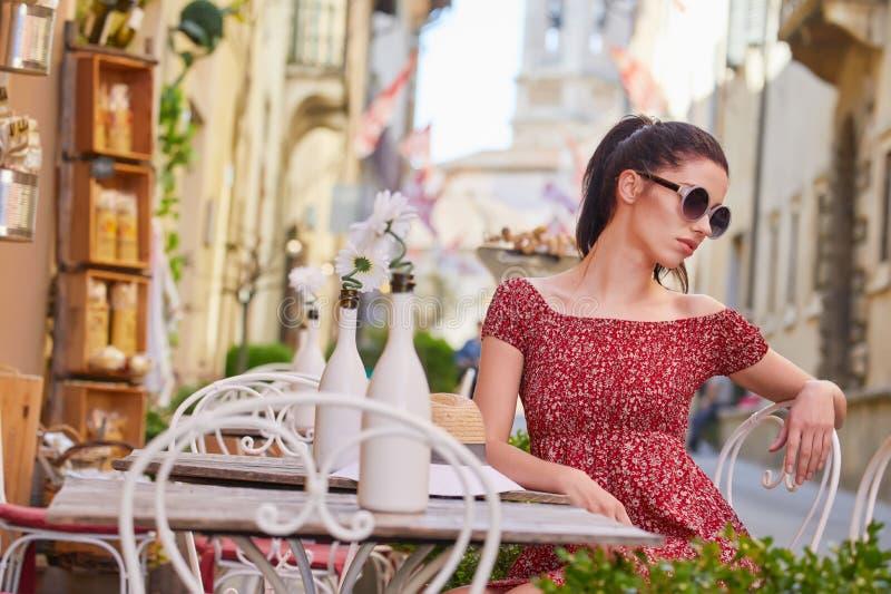 Frau, die italienischen Kaffee am Café auf der Straße in Toskana trinkt lizenzfreies stockfoto