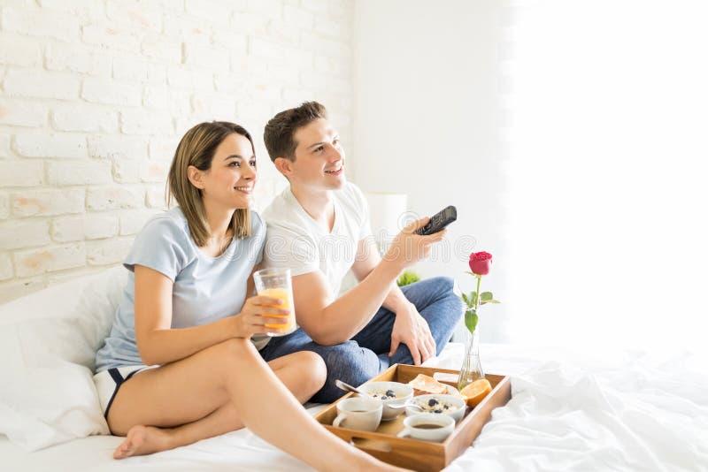 Frau, die Juice By Boyfriend Changing Channels auf Bett hat lizenzfreie stockbilder