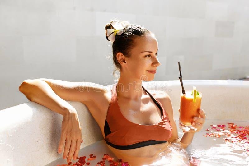 Frau, die Juice Cocktail, entspannendes Badekurort-Blumen-Bad trinkt Sommer lizenzfreies stockbild