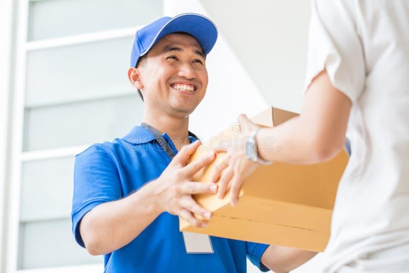Frau, die Kästen einer Lieferung vom Lieferboteen annimmt lizenzfreie stockfotos