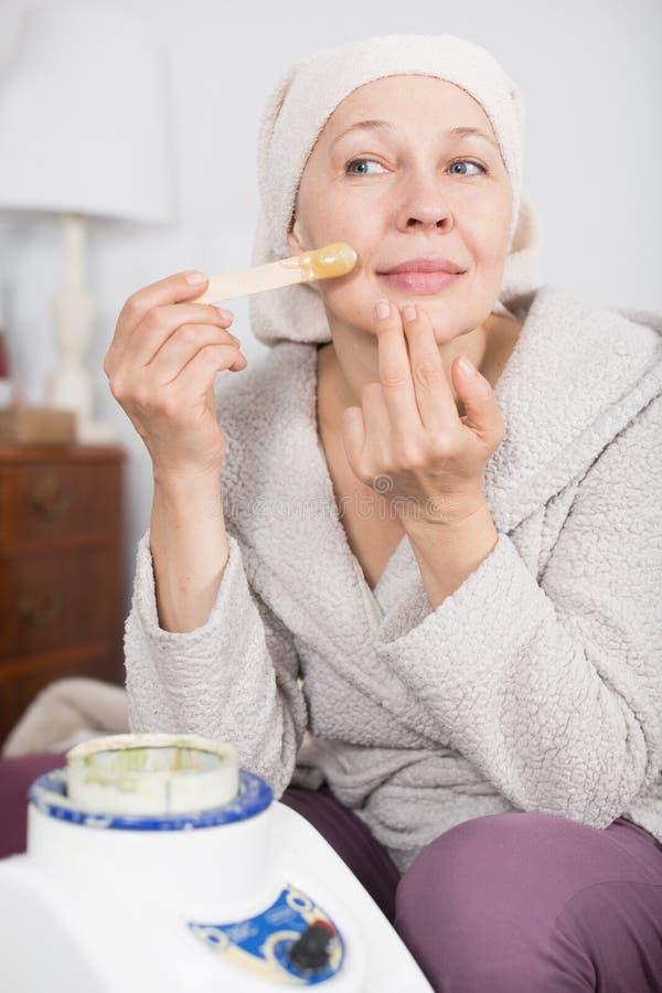 Frau, die Körperhaarabbau tut lizenzfreie stockbilder