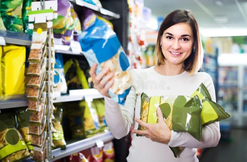 Frau, die köstliche Snäcke im Supermarkt wählt stockbilder