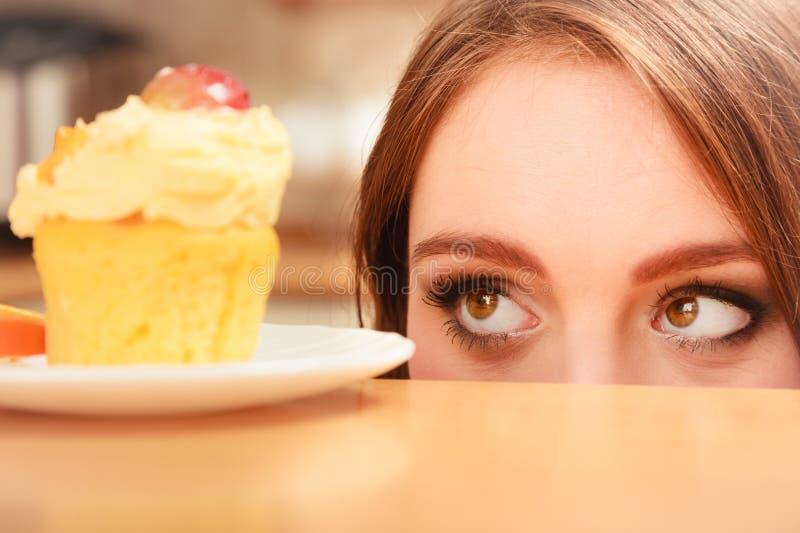 Frau, die köstlichen süßen Kuchen betrachtet gluttony lizenzfreie stockfotografie