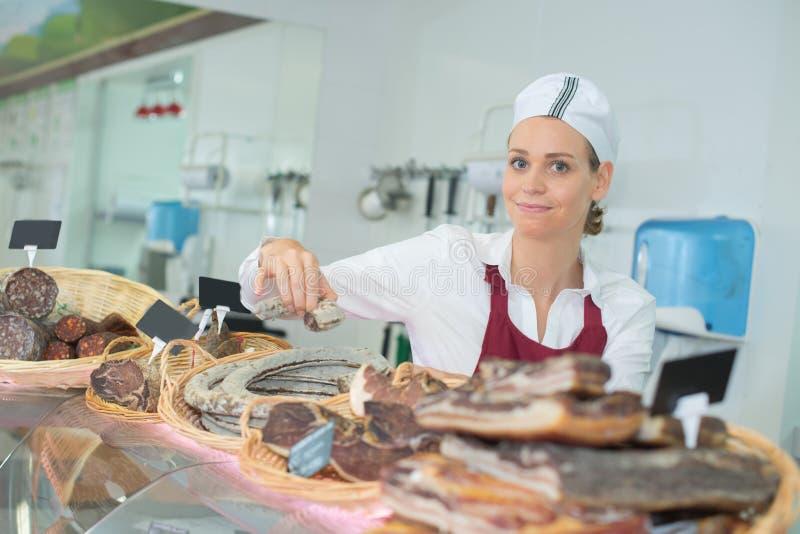 Frau, die k?stliches Prosciuttofleisch auf Markt verkauft stockfoto