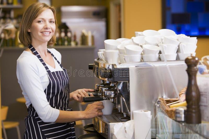 Frau, die Kaffee beim Gaststättelächeln bildet lizenzfreie stockbilder