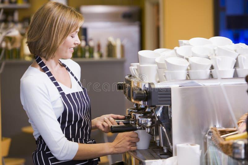 Frau, die Kaffee beim Gaststättelächeln bildet stockfoto
