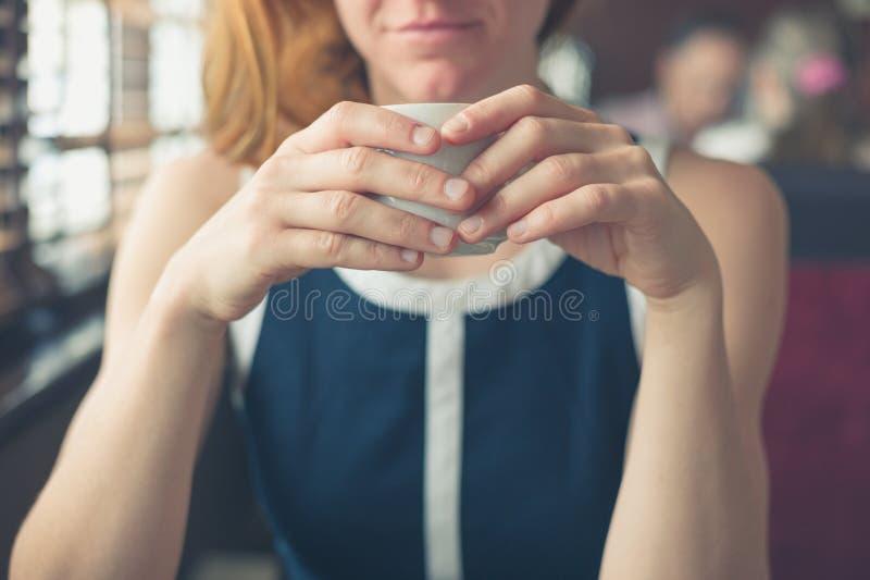 Frau, die Kaffee am Fenster in einem Restaurant trinkt lizenzfreies stockfoto