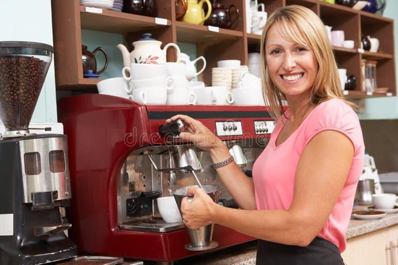 Frau, die Kaffee im Kaffee bildet lizenzfreie stockfotografie