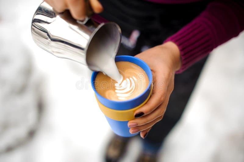 Frau, die Kaffee Lattekunst in der Kaffeestube macht stockfotografie