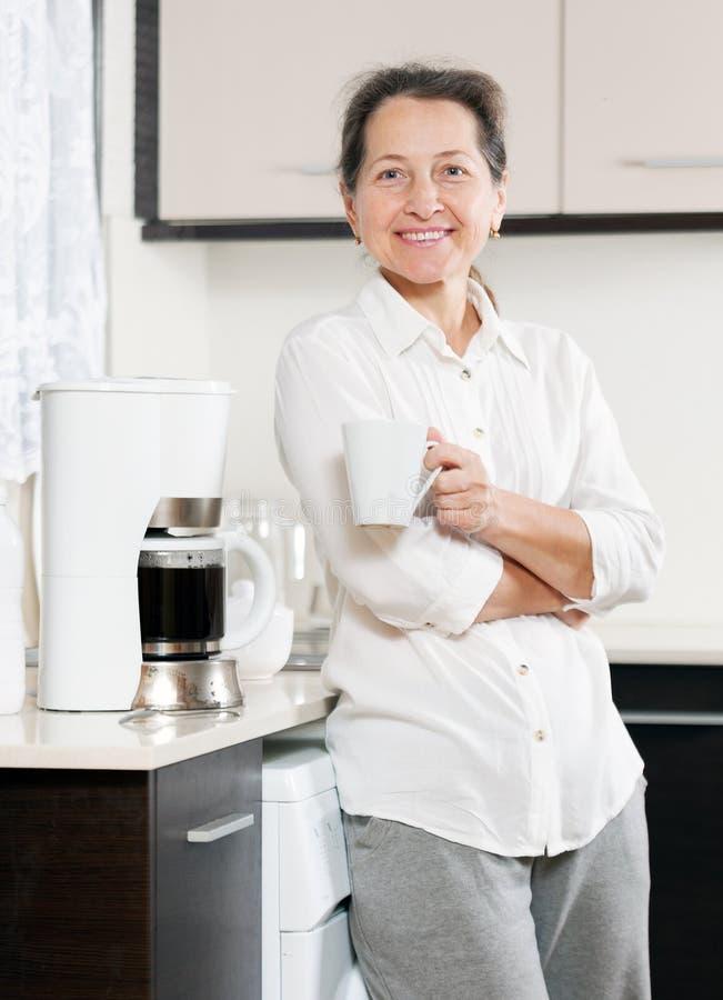 Frau, die Kaffee zubereitet lizenzfreies stockbild