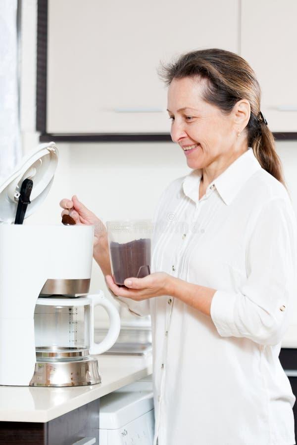 Frau, die Kaffee zum Frühstück zubereitet lizenzfreies stockbild