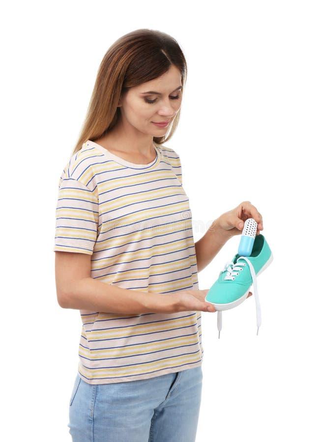 Frau, die Kapselschuherfrischungsmittel in Schuhe einsetzt lizenzfreie stockfotografie