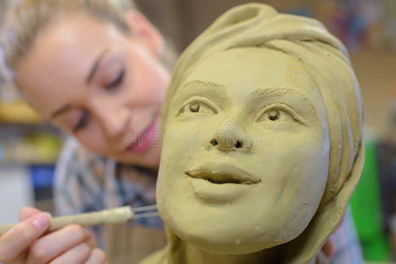 Frau, die keramisches Gesicht im Kunstunterricht macht lizenzfreie stockbilder