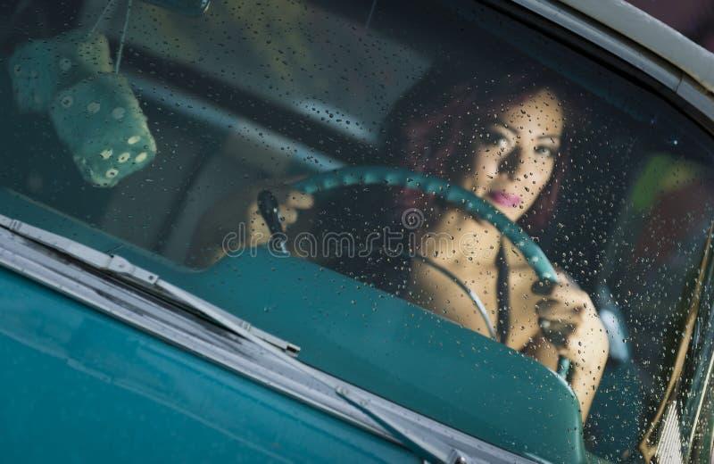 Frau, die klassisches Auto antreibt stockbild