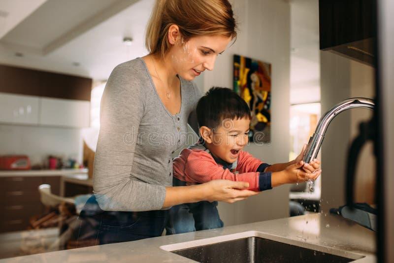 Frau, die kleinem Jungen hilft, Hände nachdem dem Kochen zu waschen lizenzfreie stockfotografie