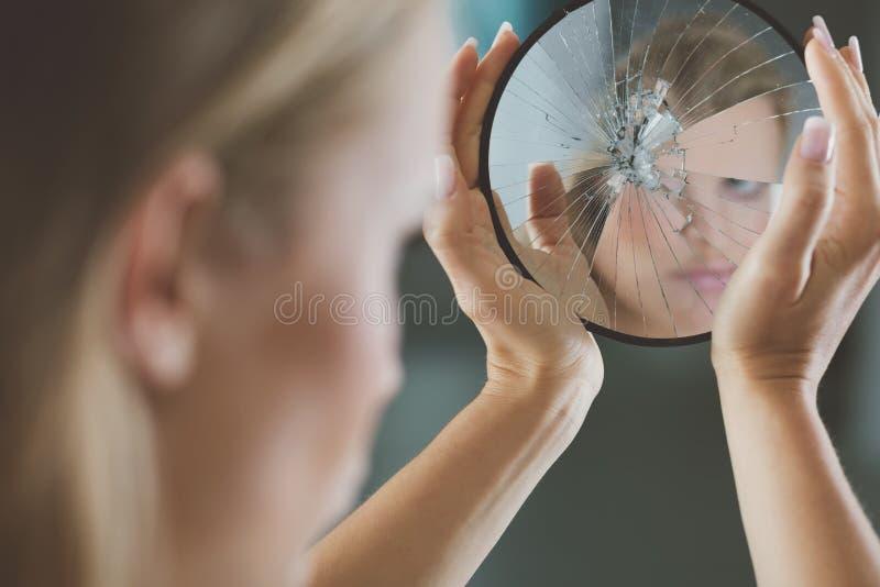 Frau, die kleinen gebrochenen Spiegel hält lizenzfreie stockfotografie