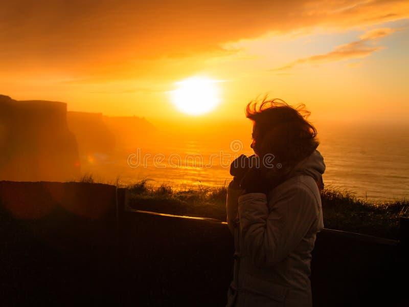 Frau, die Klippen von Moher-Sonnenuntergang in Irland betrachtet lizenzfreies stockfoto