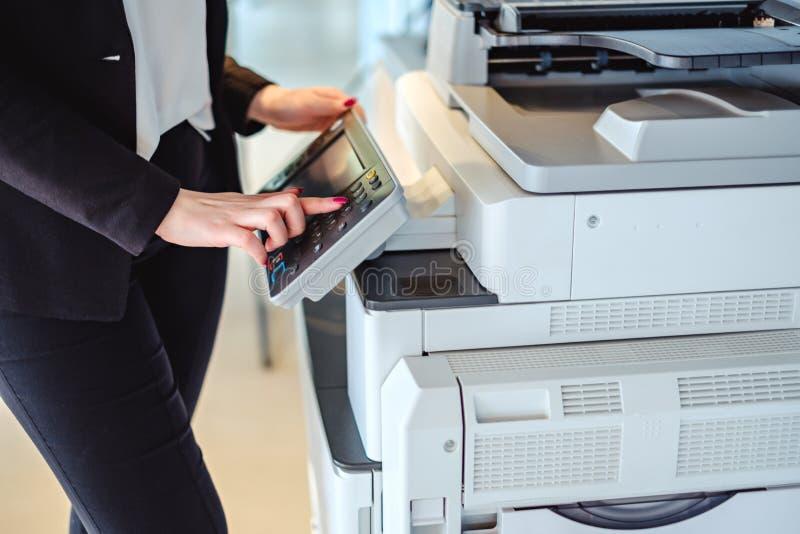 Frau, die Knopf auf einer Kopienmaschine im Büro bedrängt lizenzfreie stockfotografie
