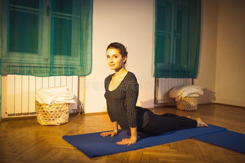 Frau, die Kobra asana Yogaübung tut stockfotografie