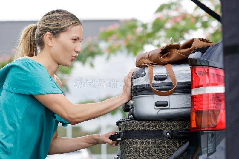 Frau, die Koffer innerhalb des Autos setzt stockbild
