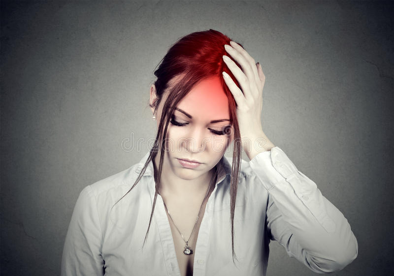 Frau, die Kopfschmerzen mit ihrem Kopf in ihrer Hand hat stockbilder