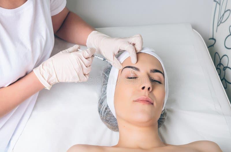 Frau, die kosmetische Einspritzung in ihrem Gesicht erhält lizenzfreie stockbilder