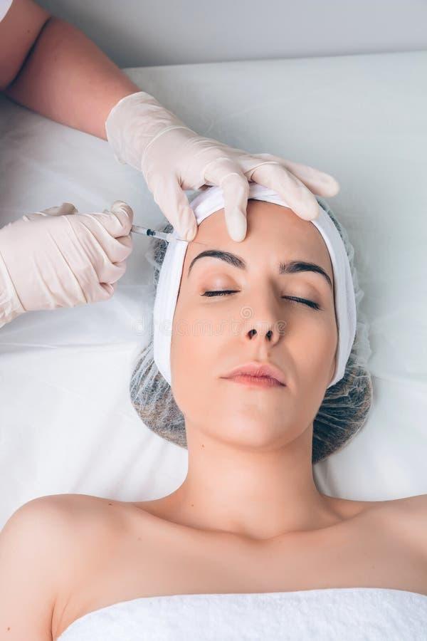Frau, die an kosmetische Einspritzung in ihrem Gesicht erhält lizenzfreie stockbilder