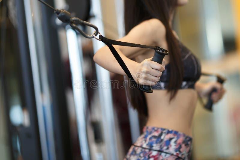 Frau, die Krafttraining an der Turnhalle tut Athlet, der an der Turnhalleneignungsunschärfe ausarbeitet stockbild
