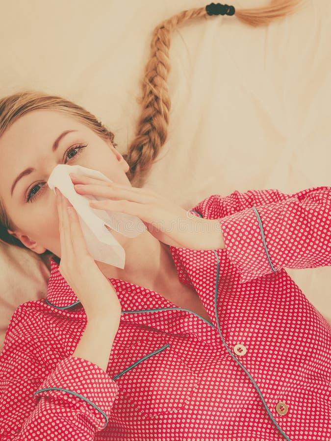 Frau, die krank ist, die Grippe habend, die auf Bett liegt stockfotografie
