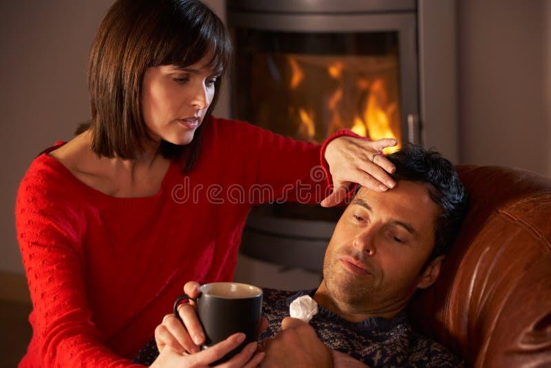 Frau, die kranken Ehemann mit Kälte wartet lizenzfreie stockfotografie